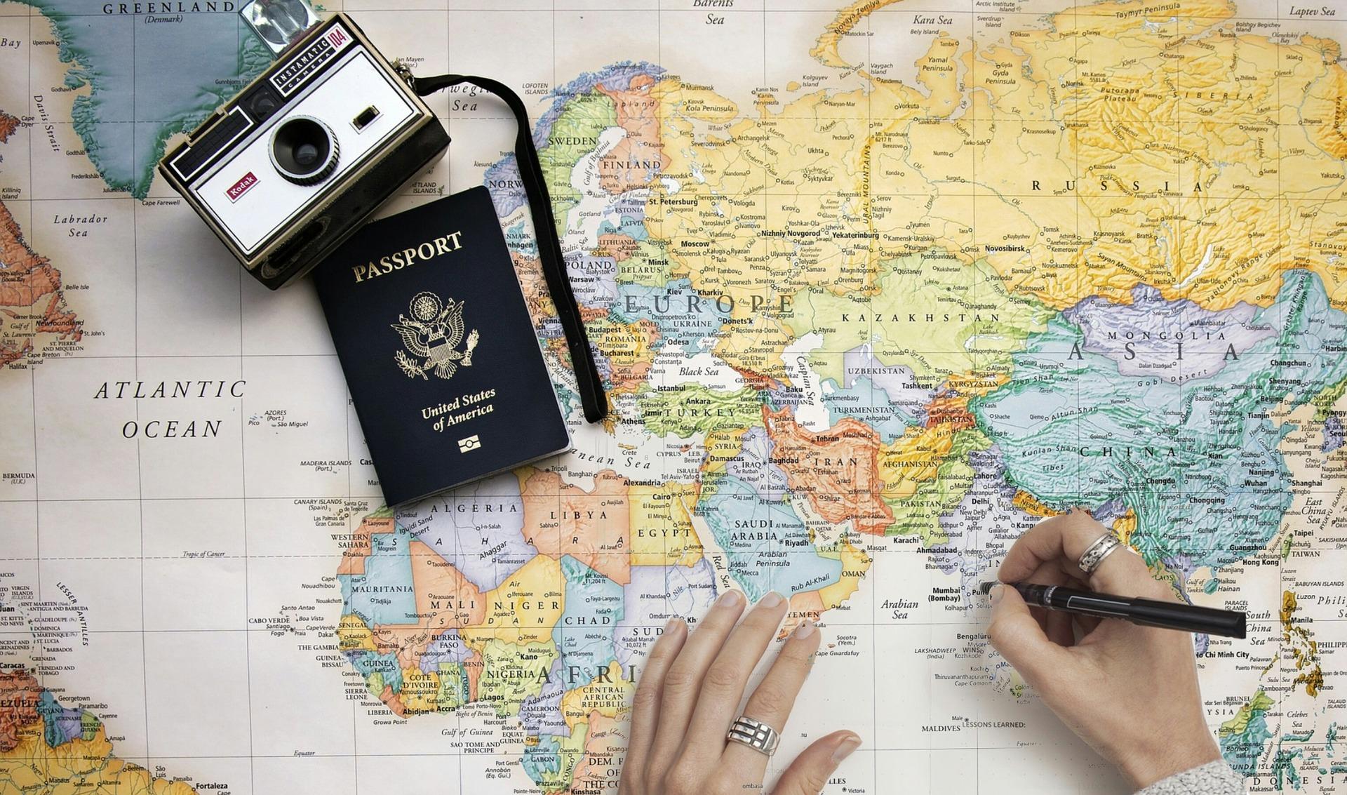 Pessoa com um mapa e seu passaporte programando viagens em grupo da melhor forma