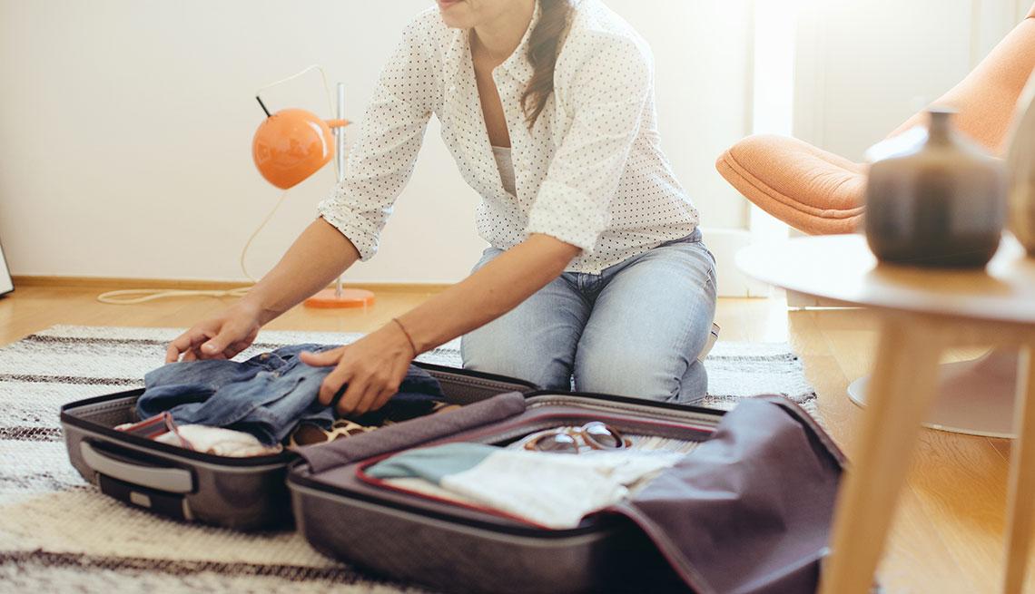 Mulher fazendo a sua mala de verão para Europa em julho