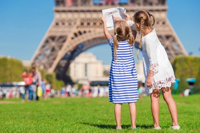 Duas meninas com um mapa em frente à Torre Eiffel com roupas de verão aproveitando a Europa em julho