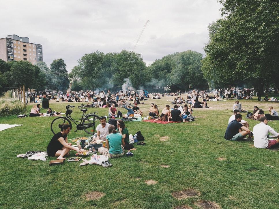 Muitas pessoas se divertindo no parque, fazendo piquenique e relaxando
