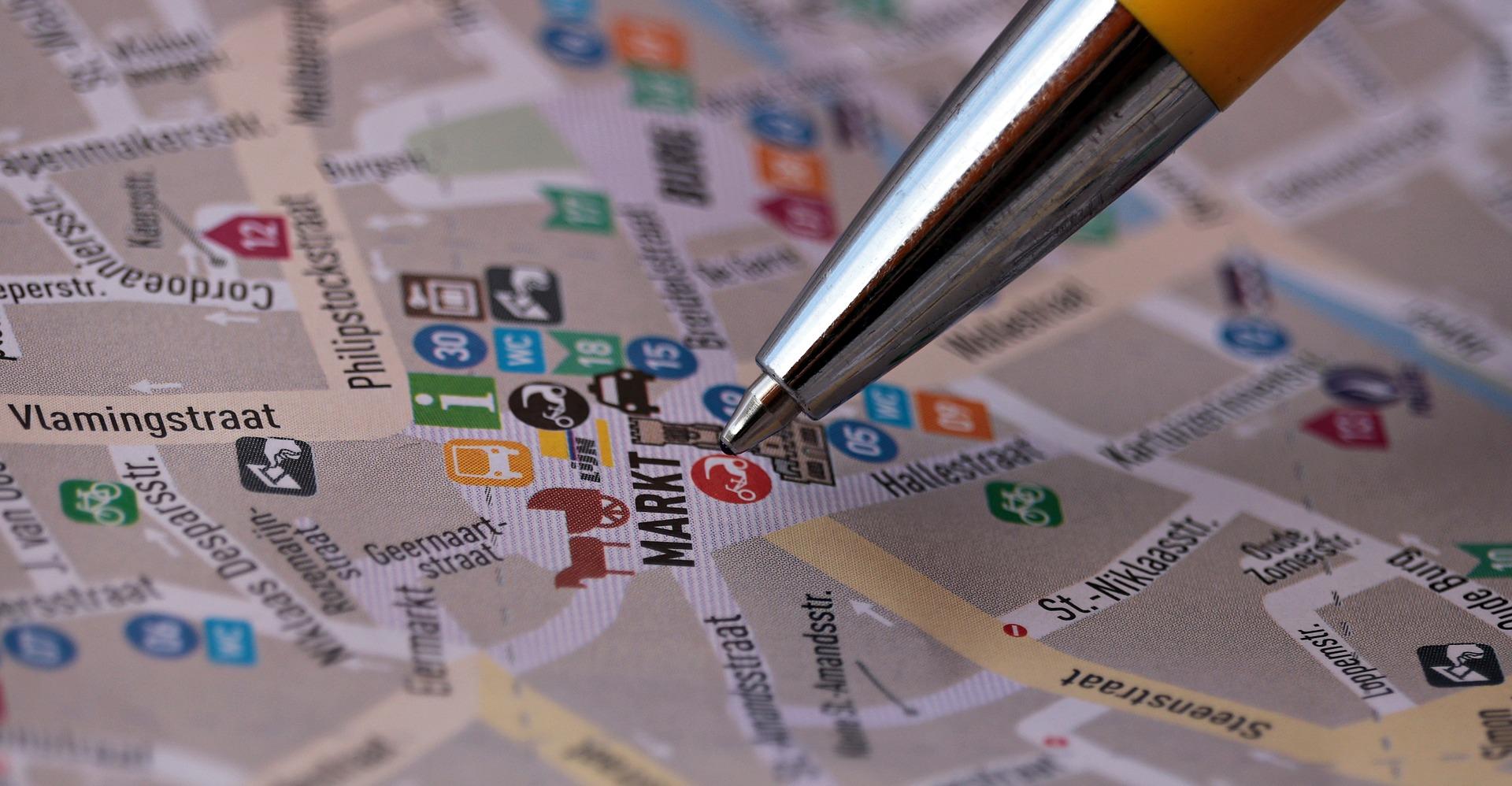 Mapa com caneta apontando para pontos importantes, planejando as viagens em grupo